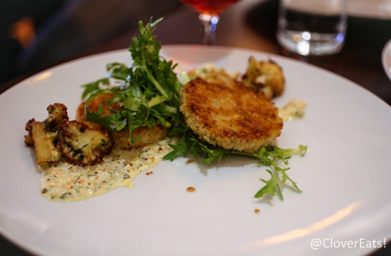 Parsnip cakes with cauliflower, mixed greens, with champagne vinaigrette and cornichon dressing