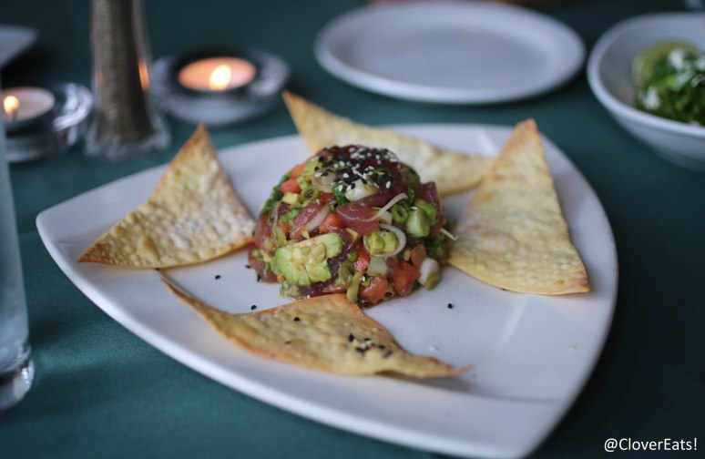 TUNA POKE - FRESH HAWAIIAN AHI TUNA, DICED & TOSSED WITH TOMATOES, SCALLIONS, & AVOCADO IN A YUZU VINAIGRETTE; SERVED ON CRISPY WONTONS WITH WASABI AND GINGER