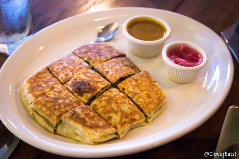 Roti Murtabak: Unleavened ghee bread filled with a mixture of ground beef, onions, eggs and fried on a griddle. Served with curry sauce and sweet and sour onion sauce