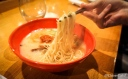 """Karaka-men """"The original """"Tonkotsu""""(pork) broth with an added kick; thin noodles with Ippudo's special blend of hot spices, topped with pork chashu, cabbage, sesame kikurage mushrooms, scallions, and fragrant garlic oil."""""""